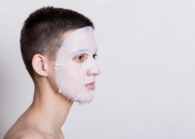 Mulher com uma máscara branca no rosto Foto gratuita