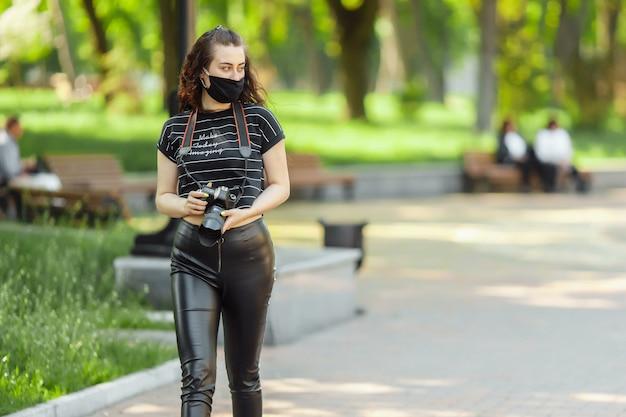 Mulher com uma máscara médica passeios no parque com uma câmera Foto Premium