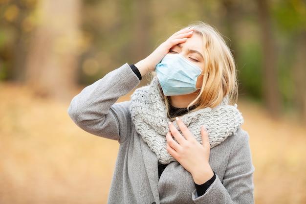 Mulher com uma máscara no parque de outono Foto Premium