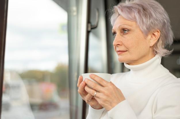 Mulher com uma xícara de café, olhando pela janela Foto gratuita