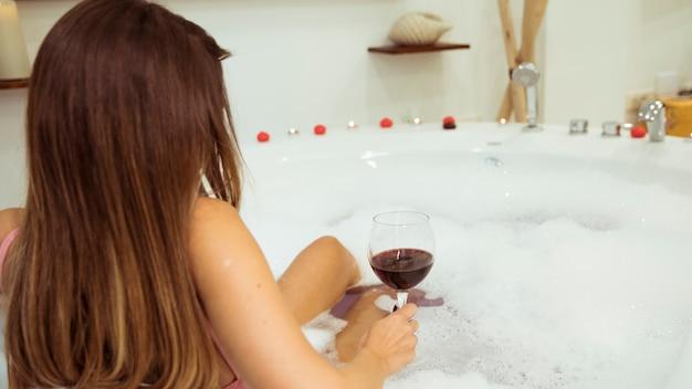 Mulher, com, vidro, em, banheira spa, com, água, e, espuma Foto gratuita