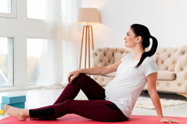 Mulher com vista lateral relaxando após se exercitar durante a gravidez Foto gratuita