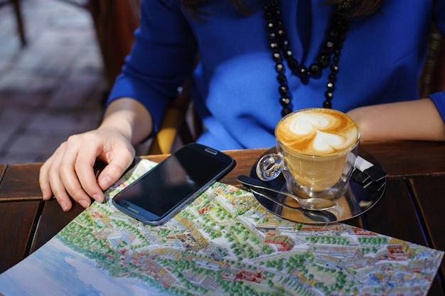 Mulher, com, xícara café, esperto, telefone, e, mapa Foto Premium