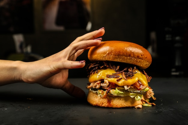 Mulher comendo hambúrguer de carne Foto gratuita