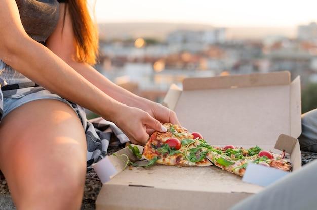 Mulher comendo pizza ao ar livre Foto gratuita