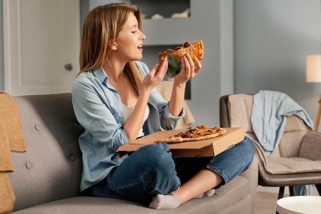 Mulher comendo pizza enquanto assiste tv Foto gratuita