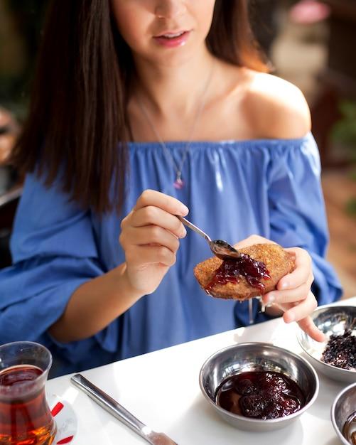 Mulher comendo rabanada com geléia de morango Foto gratuita