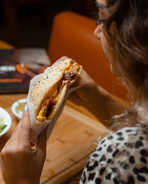 Mulher, comer kebab Foto gratuita