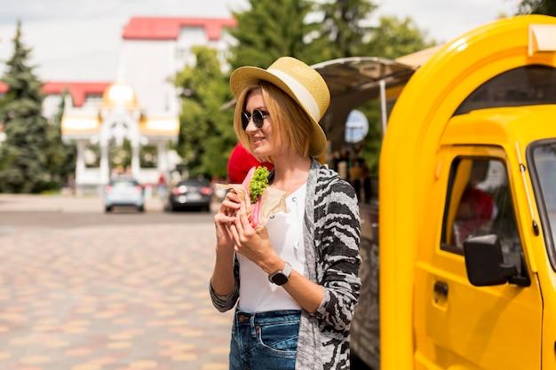 Mulher, comer, sanduíche, e, olhando Foto gratuita