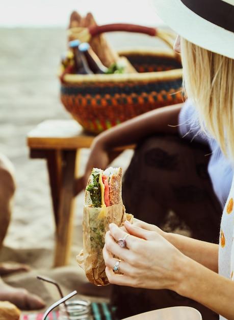 Mulher, comer, um, sanduíche, em, um, piquenique praia Foto gratuita