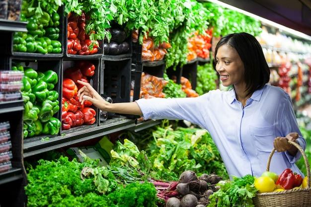 Mulher comprando legumes na seção orgânica Foto Premium
