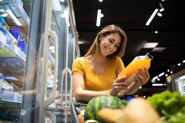 Mulher comprando mantimentos no supermercado Foto gratuita