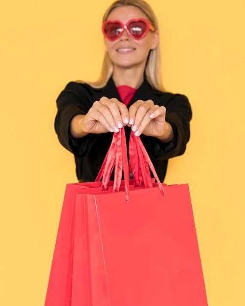Mulher comprando na sexta feira negra mostrando sacolas vermelhas Foto gratuita