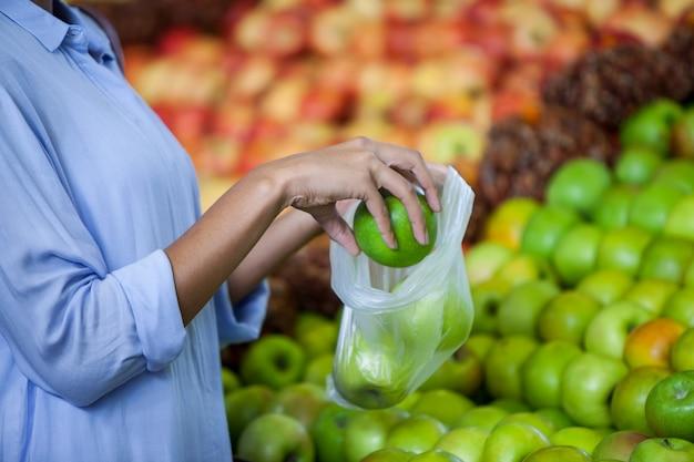 Mulher comprando uma maçã Foto Premium