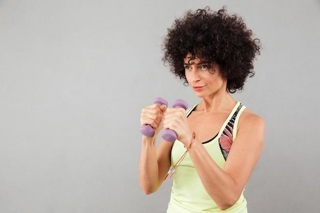 Mulher concentrada encaracolado fitness fazendo exercício com halteres Foto gratuita