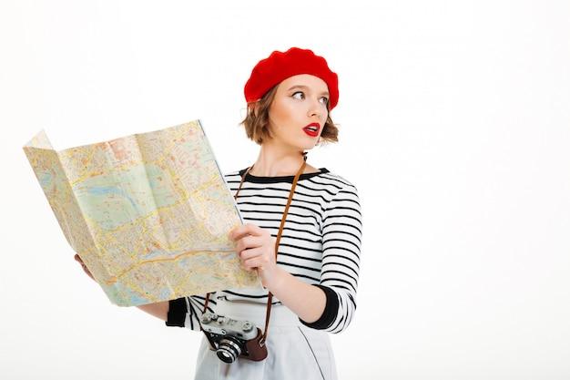 Mulher concentrada turista com câmera segurando o mapa. Foto gratuita