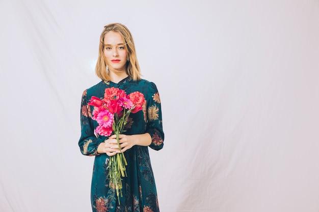 Mulher confiante atraente com buquê de flores Foto gratuita