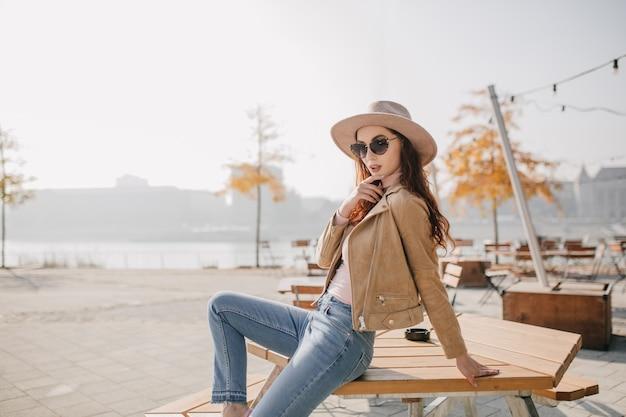 Mulher confiante em calças jeans, sentada na mesa de um café de rua Foto gratuita