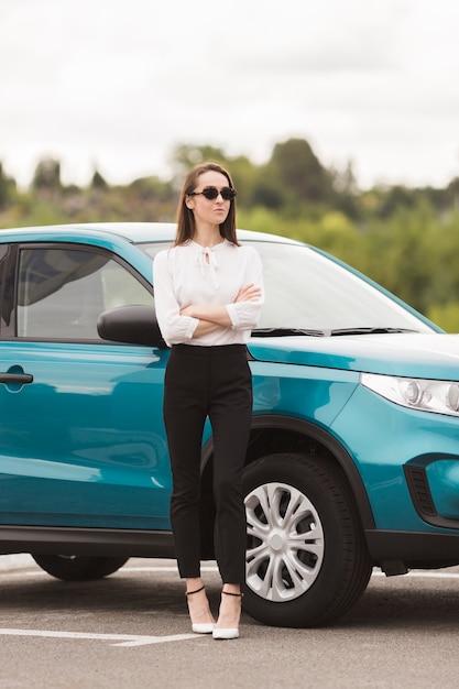 Mulher confiante posando na frente de um carro Foto gratuita