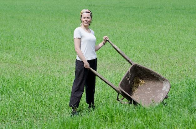 Mulher confiante trabalhando com um carrinho de mão em uma fazenda Foto gratuita