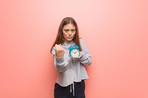 Mulher consideravelmente caucasiano dos jovens que mostra o punho para frontear, expressão irritada. ela está segurando um despertador. Foto Premium
