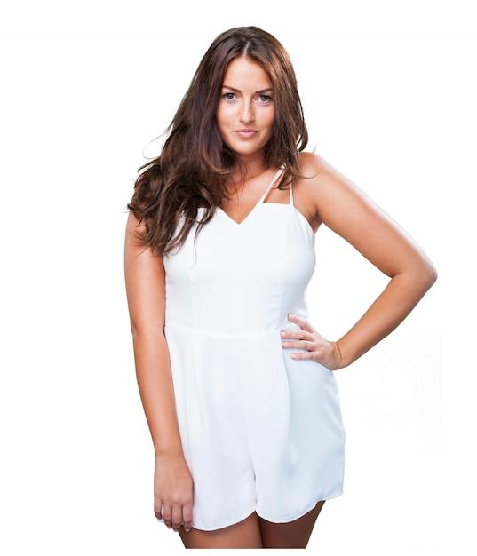 Mulher consideravelmente nova que desgasta um vestido branco Foto gratuita