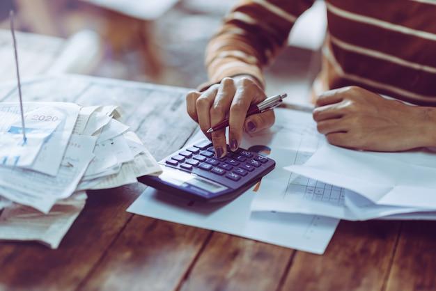 Mulher contando o salário das finanças, usando a calculadora, pressionando as pessoas. Foto Premium