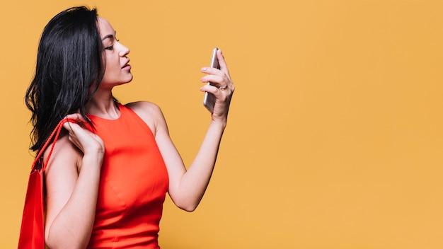 Mulher contemporânea com telefone e sacola de compras Foto gratuita