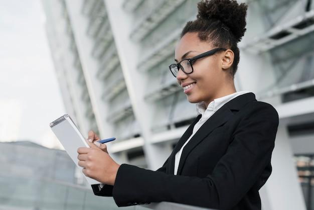 Mulher corporativa, escrevendo no caderno Foto gratuita