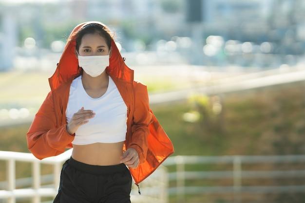 Mulher corredores exercício matinal, ela usa uma máscara nasal. proteção contra poeira e vírus Foto gratuita