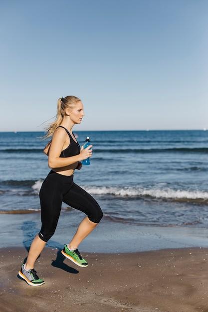 Mulher correndo na praia | Foto Grátis