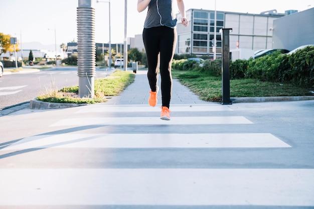 Mulher cortada que corre no crosswalk Foto gratuita