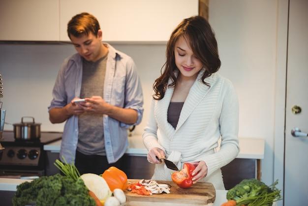 Mulher cortando legumes e homem usando telefone celular na cozinha Foto gratuita