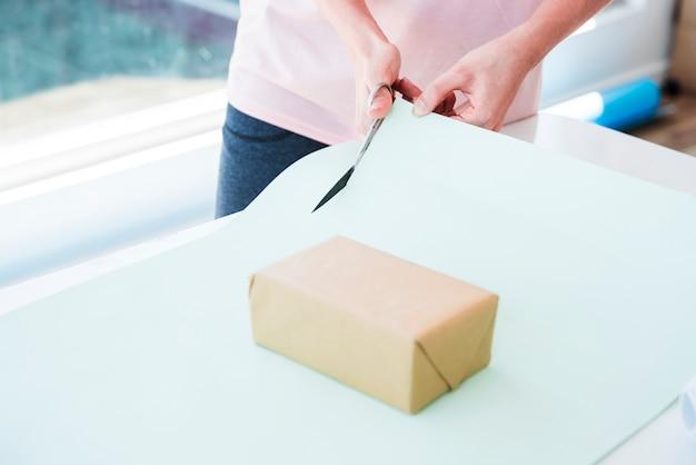 Mulher, corte, papel cartão, com, scissor, para, embrulhando, a, caixa presente Foto gratuita
