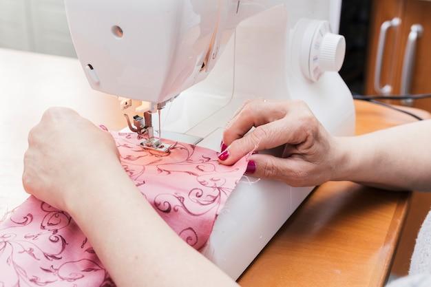 Mulher costura o pano em uma máquina de costura sobre a mesa de madeira Foto gratuita
