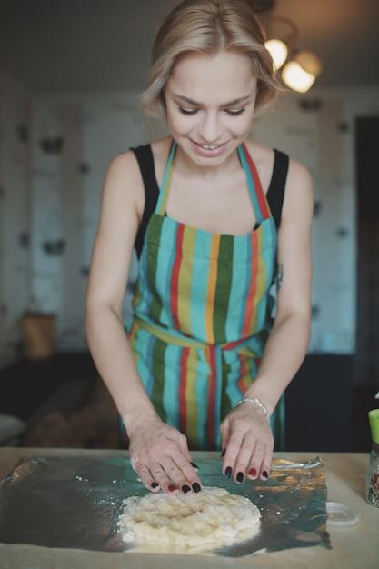Mulher cozinhando pizza na cozinha Foto gratuita