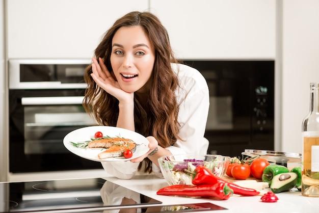 Mulher, cozinhar, peixe, prato, cozinha Foto Premium