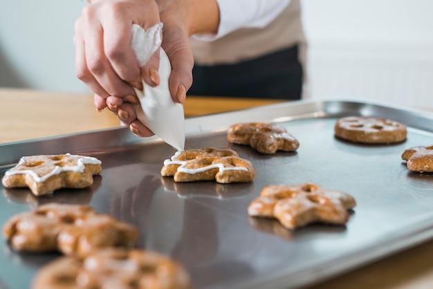 Mulher, creme aplicando, para, natal, biscoitos frescos, ligado, bandeja Foto gratuita