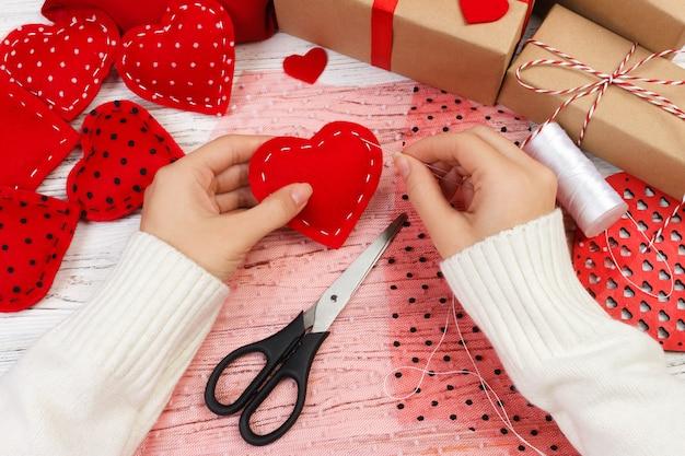 Mulher criando coração vermelho na mesa de madeira. presente para o dia de são valentim artesanal Foto Premium