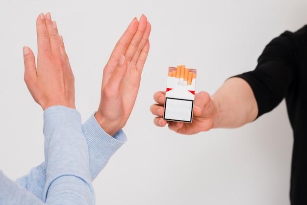 Mulher, cruzado, mãos, recusar, um, cigarro, oferta, por, dela, amigo masculino Foto gratuita