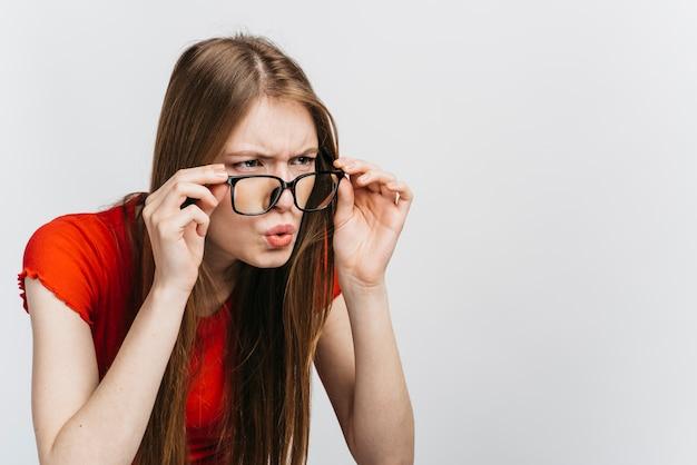 Mulher curiosa usando óculos olhando com espaço de cópia Foto gratuita