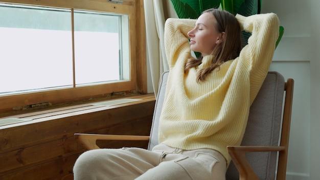 Mulher curtindo momentos de tranquilidade e conforto relaxando na poltrona em casa Foto Premium