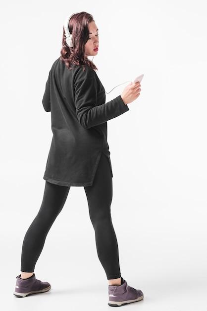 Mulher curtindo música no fone de ouvido contra o pano de fundo branco Foto gratuita