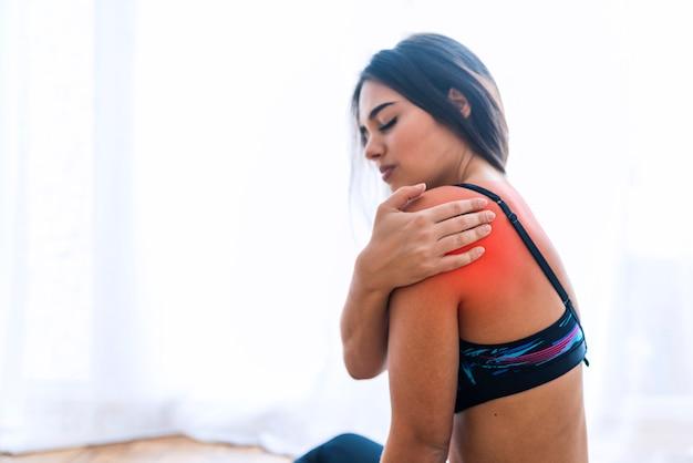 Mulher da aptidão que sofre da lesão no ombro durante o exercício. copie o fundo do espaço. Foto Premium