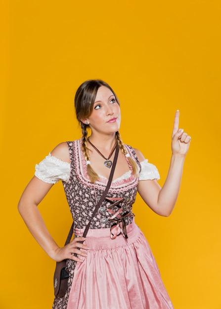 Mulher da baviera, apontando para cima Foto gratuita