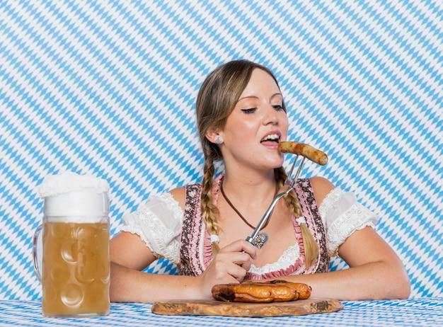 Mulher da baviera degustação bratwurst alemão Foto gratuita