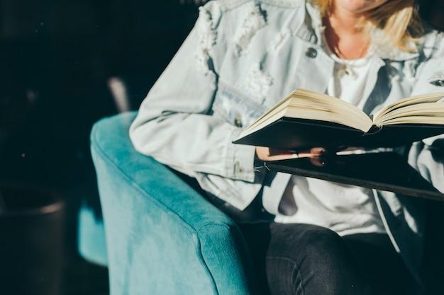 Mulher da colheita que aprecia o livro no café Foto gratuita