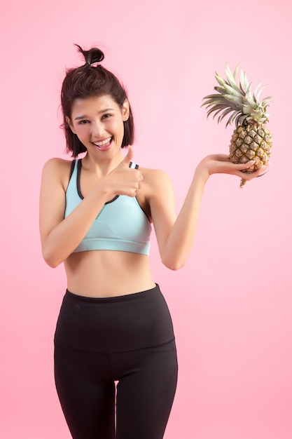 Mulher da fruta do abacaxi que sorri saudável e alegre após o exercício para controlar o peso Foto gratuita