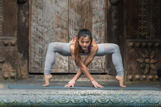 Mulher da ioga que faz o exercício com pose da ioga em casa. Foto Premium