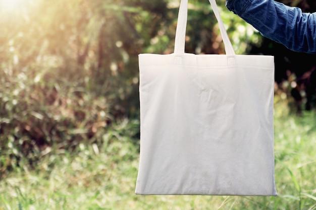 Mulher da mão que guarda a sacola do algodão no fundo da grama verde. conceito eco e reciclagem Foto Premium